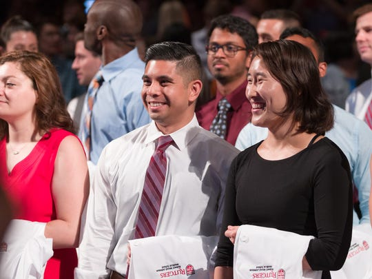 Cedric Magaway, left, and Joyce Lu, right, incoming medical students at Rutgers Robert Wood Johnson Medical School, wait for the start of the White Coat Ceremony at the State Theatre in New Brunswick.