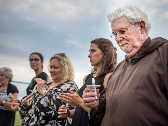 Fr. John Boylan of Christ the Prophet Church in Spring Hill, Tenn, holds a candle as protesters gather outside of the Riverbend Maximum Security Institution against the execution of Billy Ray Irick in Nashville, Tenn., Thursday, Aug. 9, 2018. Irick, 59, was convicted in 1986 on charges of raping and murdering Paula Dyer, a 7-year-old Knox County girl.