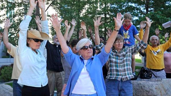 Reno protesters raise their hands during a moment of silence, at the Thompson Federal Building in downtown Reno on August 14, 2014, in honor of Michael Brown who was killed by police in Missouri.