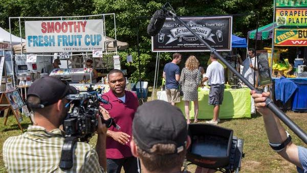 The Food Network's Anthony Anderson talks to the cameras as judges try the ice cream at the Scrumptious booth during filming  at the Old Fashioned Ice Cream Festival at Rockwood Park on Sunday.  .