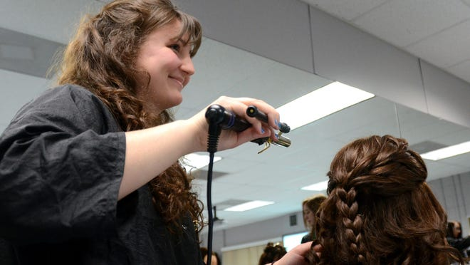 Tina Ponessa looks up while styling the hair on a mannequin Mon, April 13, during cosmetology class at RESA.