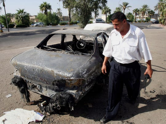 An Iraqi traffic policeman inspects a car destroyed by a Blackwater security detail in al-Nisour Square in Baghdad, Iraq, in September 2007. Four former security contractors are on trial in Washington, D.C, in connection with the deaths of civilians in that shooting. The New York Times reported Sunday evening that a State Department investigation was abandoned and the chief investigator charged in a previously undisclosed report that Blackwater appeared to be acting above the law in Iraq.