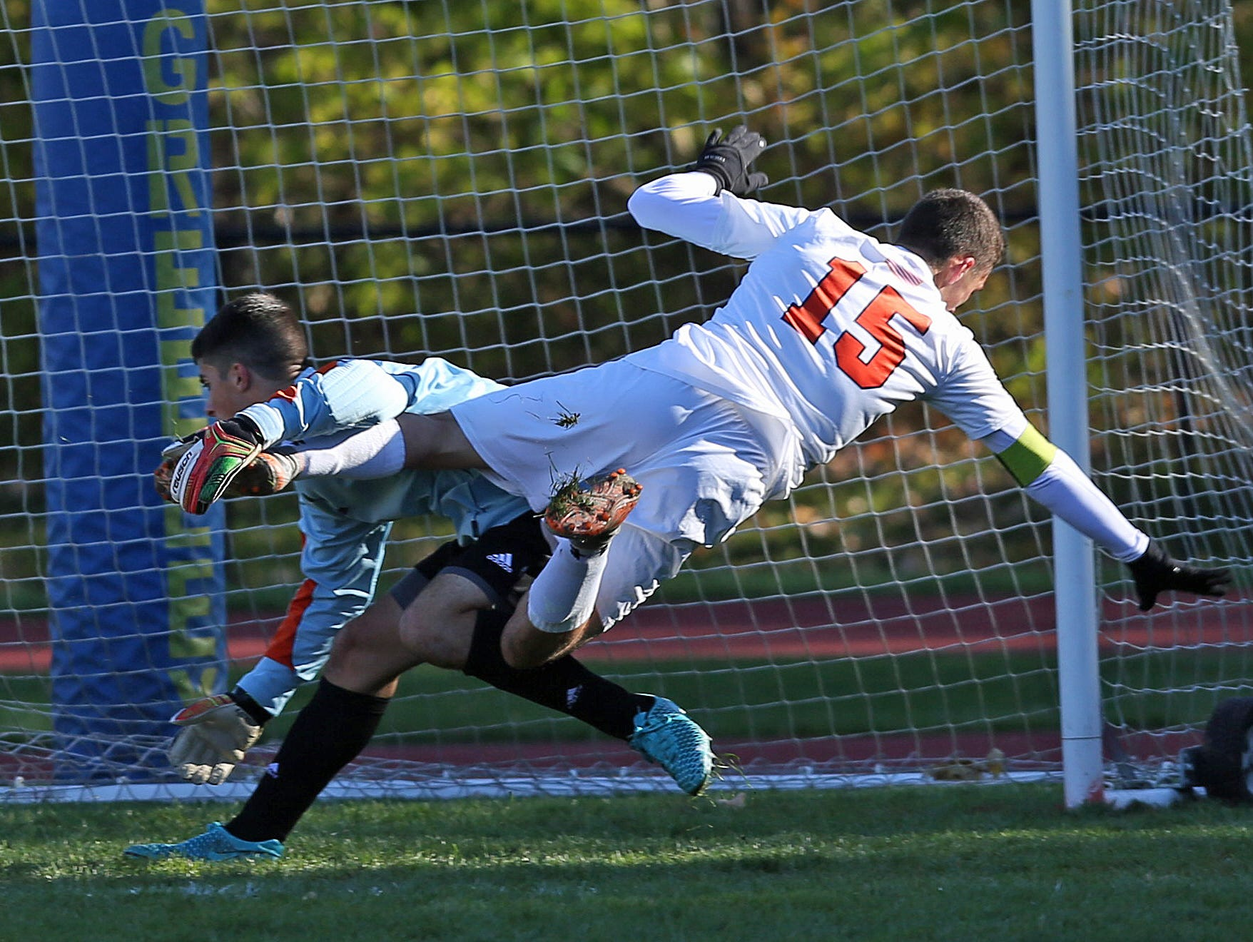 Greeley's Matt Neuberger (15) flips over North Rockland goal keeper Julio Rebolledo as he score his third of three first half goals during a boys soccer playoff game at Horace Greeley High School in Chappaqua Oct. 23, 2015.