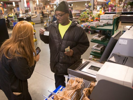A customer shows ID to purchase alcohol on  the first day of legal universal Sunday carry-out alcohol sales in Indianapolis on March 4, 2018.