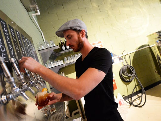 Bartender Greg Collister pours a beer at Columbia Kettle