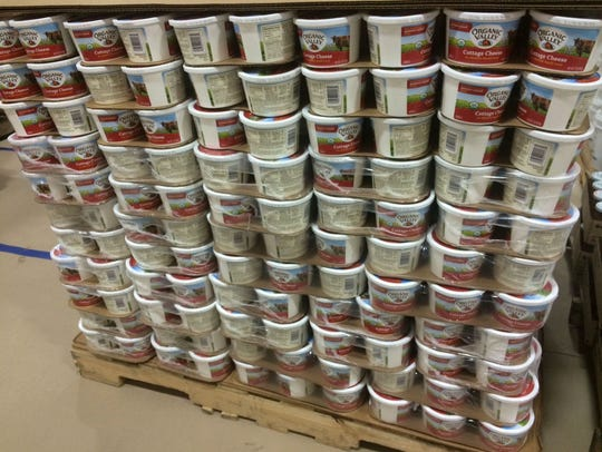 Cartons of cottage cheese are stacked on a pallet in