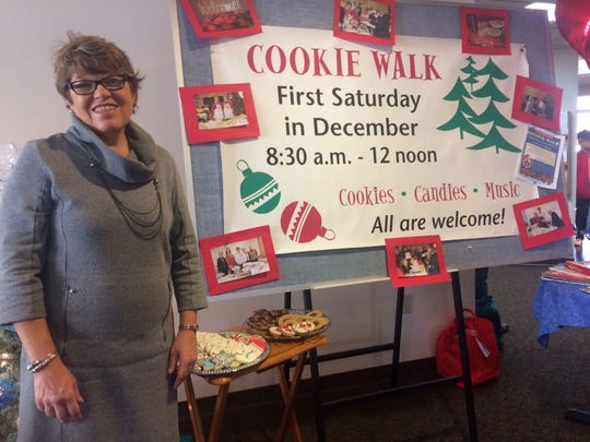 Event coordinator Jane Laubenstein stands next to a display that includes plates of assorted cookies and candies for the 30th annual Cookie Walk, which will be Dec. 3 at First United Church of Christ in Green Bay. All proceeds from the popular event go to local outreach.