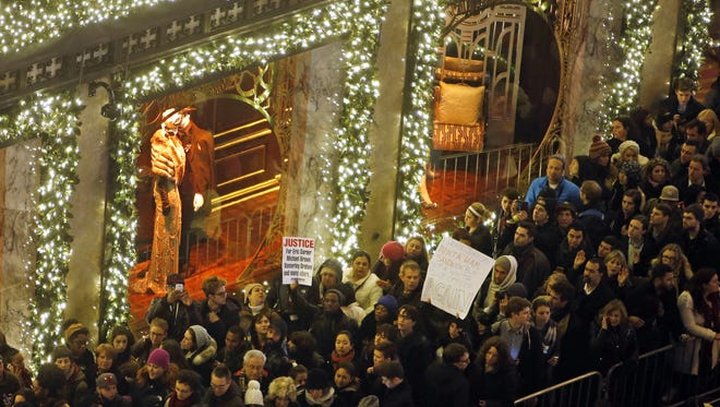 A group of protesters with signs makes their way up a congested Fifth Avenue sidewalk near Rockefeller Center as they rally against the decision not to indict the police officer involved in the death of Eric Garner during a ceremony to light the Rockefeller Center Christmas tree, Wednesday, Dec. 3, 2014, in New York. (AP Photo/Jason DeCrow)