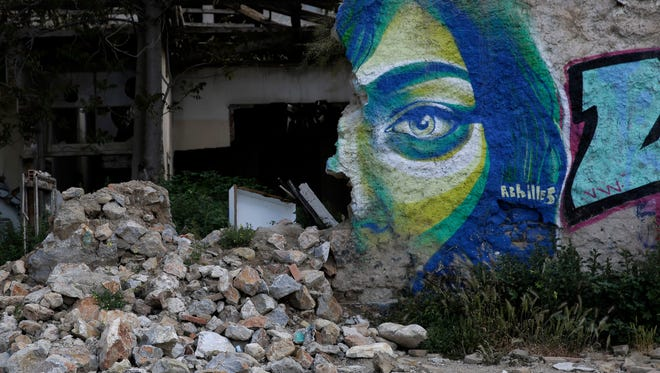 Graffiti by Greek street artist Achilles is seen on a wall of an abandoned house in central Athens.