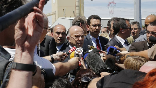 French Interior Minister Bernard Cazeneuve answers reporters after an attack took place, Friday in Saint-Quentin-Fallavier, southeast of Lyon, France.  At least one man attacked a gas factory Friday in southeastern France, posting a severed head at the factory's entrance along with banners covered with Arabic writing, officials said. France immediately opened a terrorism investigation.