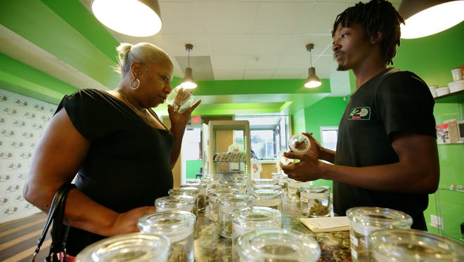 Salesman Floyd Hardrick, right, 24, of Detroit assists Lisa Price, 55, of Detroit at 420 Dank. Price is suffering from degenerative disc disease and has a medical marijuana license.