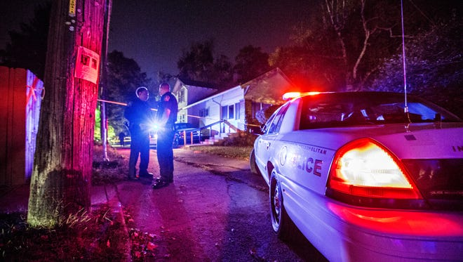 Two IMPD officers stand at the mouth of an alley near 42nd Street and Byram Avenue where a man was found dead Tuesday, Oct. 13, 2015.