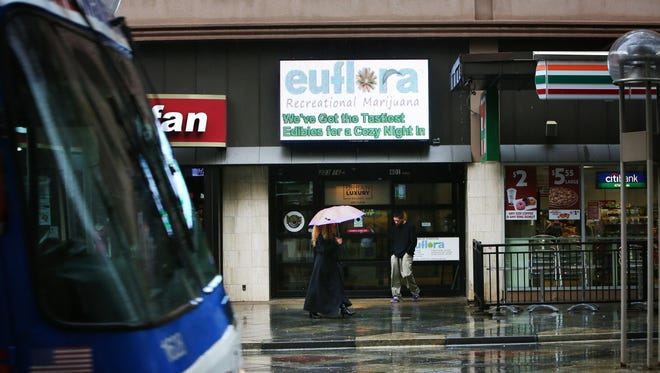 People walk past euflora recreational marijuana retail shop in downtown Denver.