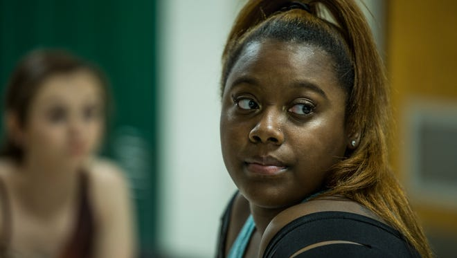 Chyna Johnson glances over her shoulder in the hallway of Broad Ripple High School as she warms up to perform in her final dance recital.