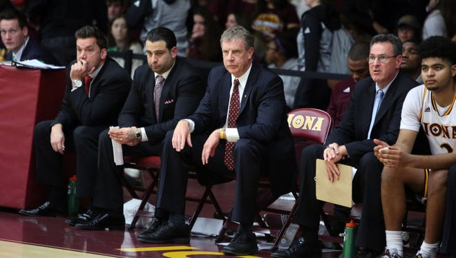 Iona College head coach Tim Cluess, center, is pictured seated to the left of associate head coach Jared Grasso during the team's home opener against Niagara, Dec. 4, 2016 in New Rochelle.