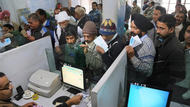 Indians stand in line to deposit discontinued notes in a bank in Jammu, India, on Dec. 30, 2016.