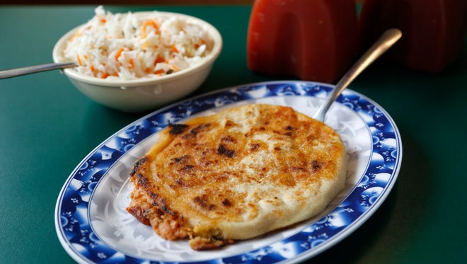 A pork pupusa (center) is served with a cabbage salad and salsa Wednesday, March 1, 2017 at the Salvadorian restaurant La Cuscatleca in Des Moines.