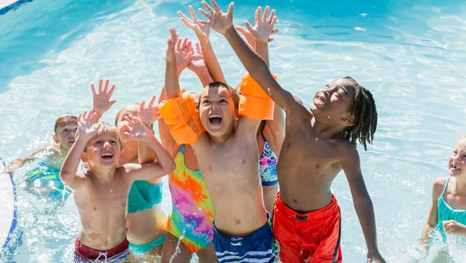 A multi-ethnic group of children, 5 to 7 years old, playing in a swimming pool. They are raising their arms, looking up, getting ready to catch something.