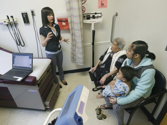 Vietnamese interpreter Anh Ta translates to Tam Nguyen and her daughter Phung Duong who holds her son Minh Nguyen, 1, at Jordan Health on Lake Avenue. The family lives in Rochester.