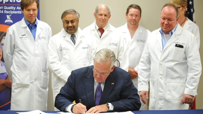 Doctors from St. Mary's Hospital stand behind Gov. Jay Nixon as he signs new legislation Thursday in Jefferson City regarding medical malpractice. Nixon signed a measure Thursday capping some damage awards in medical malpractices cases, three years after the state's Supreme Court struck down similar limits as unconstitutional.