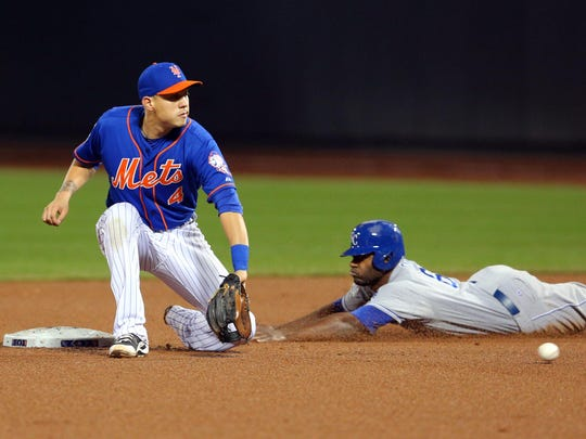 Nov 1, 2015; New York City, NY, USA; Kansas City Royals center fielder Lorenzo Cain (6) steals second base ahead of the throw to New York Mets shortstop Wilmer Flores (4) in the 9th inning in game five of the World Series at Citi Field. Mandatory Credit: Brad Penner-USA TODAY Sports