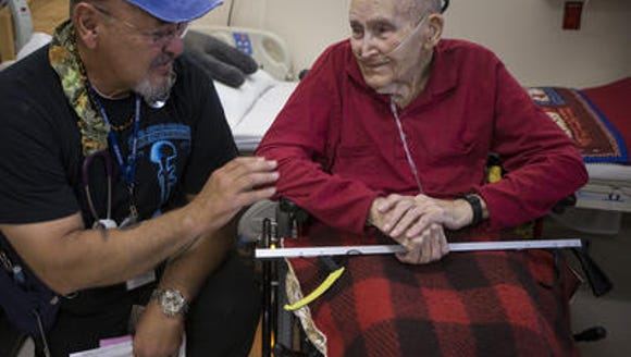 Registered nurse Joseph Leal kneels to talk with 93-year-old