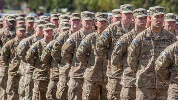 Members of the 153rd Military Police Company stand at ease as they listen to speakers at homecoming ceremonies in Delaware, City, Delaware on Sept. 28, 2013. The 153rd returned after nine months in Afghanistan.