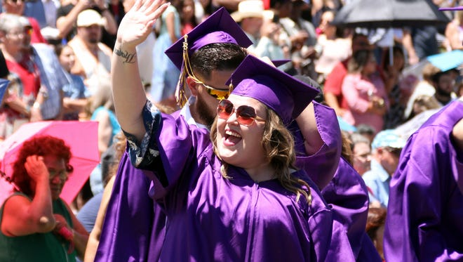 Alexandra Ortiz waves to her family members as she entered Old James Stadium for Saturday's 2018 Spring Commencement Exercise at Western New Mexico University in Silver City, NM.