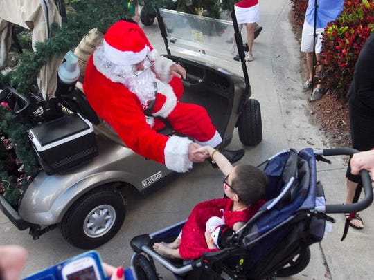 Santa greets Miranda Gonzalez, 4, after arriving by helicopter at Lexington Country Club to visit patients from Golisano Children's Hospital on Saturday. After lunch, the children and their siblings were given Christmas gifts.