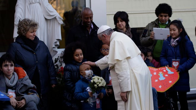 "Pope Francis caresses a child as he arrives at the ""Bambin Gesu'"" children's hospital in Rome."