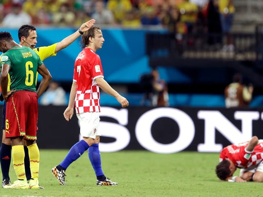 Referee Pedro Proenca from Portugal gestures after giving a red card to Cameroon's Alex Song (6) as Croatia's Ivan Rakitic looks on during the group A World Cup soccer match between Cameroon and Croatia at the Arena da Amazonia in Manaus, Brazil, Wednesday, June 18, 2014.  (AP Photo/Themba Hadebe)