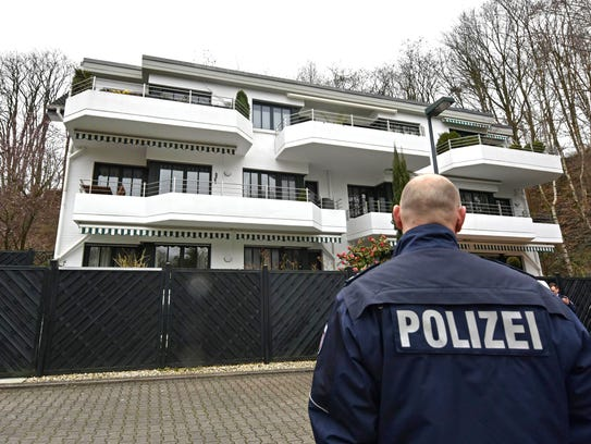 A police officer stands in front of an apartment building