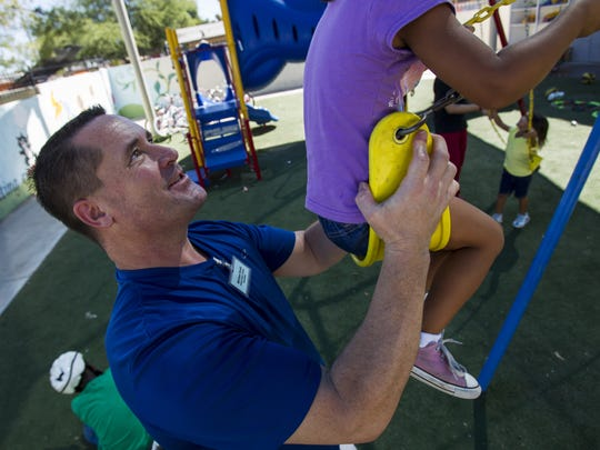 Michael Scott pushes a child on a swing set at the Child Crisis Center in Mesa.