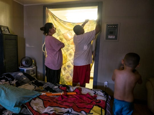 The father of a family of four uses a sheet to close off the small kitchen from the one room apartment they are renting at Airport Motel in Plainview, Texas, on Aug. 18, 2015.  Throughout the Panhandle and West Texas, motels often serve as housing of last resort for farmworkers.