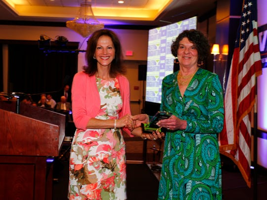 Kathi Roberts, left, presents Maureen Wilson of Pyramid Brokerage Company 2016 civic leader of the year award during the Greater Binghamton Chamber of Commerce's 52nd annual dinner and meeting in Binghamton on Tuesday, May 17, 2016.
