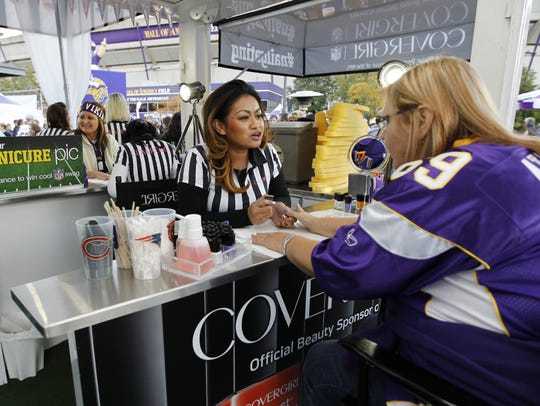 Football fans sit at the CoverGirl Nailgating booth