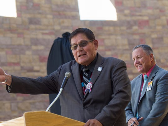 Navajo Nation Speaker LoRenzo Bates and San Juan County Chief Executive Officer Kim Carpenter participate in an unveiling ceremony for a monument dedicated to the Navajo Code Talkers Friday at the San Juan County Administration Offices in Aztec.