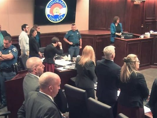 In this image made from Colorado Judicial Department video, Arlene Holmes, top right, the mother of James Holmes, third from left, in white shirt, stand for the jury to leave for a break in testimony during the sentencing phase of the Colorado theater shooting trial in Centennial, Colo., on Wednesday, July 29, 2015.