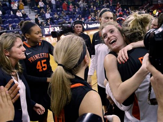 Blake Dietrick, right facing camera, hugs a teammate as Princeton head coach Courtney Banghart, left, and teammate Leslie Robinson (45) look on after the regular-season finale.