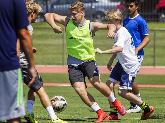 Steven Siegfried (center) cuts through defenders in passing drills at practice at Tower Hill School in Wilmington on Wednesday morning.