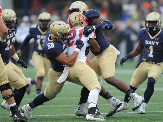 Navy's Daniel Gonzales, left, stops VMI's Jabari Turner during the second quarter of an NCAA college football game Saturday, Oct. 11, 2014, in Annapolis, Md. (AP Photo/Capital Gazette, Paul W. Gillespie)