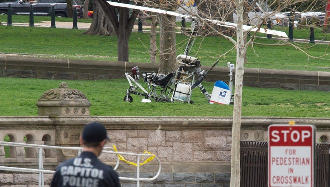 """A mini helicopter or gyrocopter that landed on the US Capitol South Lawn area is viewed April 15, 2015, in Washington, DC. A man flying a mini helicopter illegally landed his aircraft on the west lawn of the US Capitol Wednesday, triggering street closures around the building and prompting a police investigation.""""The US Capitol Police continues to investigate, with one person detained,"""" USCP officer Shennell Antrobus told AFP. A robotic police device was seen close to the mini helicopter, apparently inspecting it. AFP PHOTO/PAUL J. RICHARDSPAUL J. RICHARDS/AFP/Getty Images ORIG FILE ID: 539750596"""