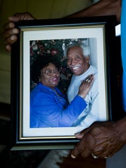 Marvin Porter holds a portrait of him and his wife