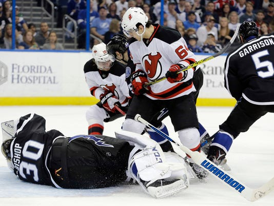 New Jersey Devils center Joseph Blandisi (64) knocks the stick away from Tampa Bay Lightning goalie Ben Bishop (30) during the first period of an NHL hockey game Saturday, April 2, 2016, in Tampa, Fla. Blandisi was penalized for interference. (AP Photo/Chris O'Meara)