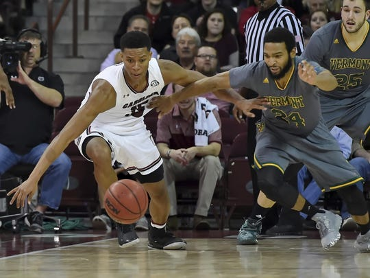 South Carolina's PJ Dozier, left, battles Vermont's Dre Wills for a loose ball during the first half of an NCAA college basketball game against Vermont on Thursday in Columbia, S.C.