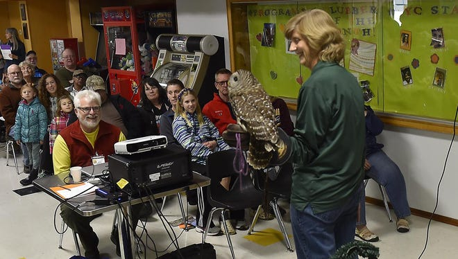 Kim Diedrich, chief naturalist of the Bay Beach Wildlife Sanctuary in Green Bay, shows celebration participants a barred owl as she tells them about the raptor's characteristics and habitat. Diedrich also brought a live red-tailed hawk to the event.
