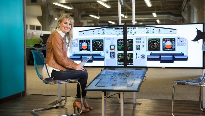 Kerry Frank, co-founder and chief executive officer of Comply365, in front of the flight simulator in the company office.