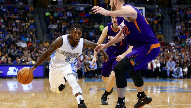 Denver Nuggets guard Nate Robinson (5) dribbles the ball against Phoenix Suns center Miles Plumlee (22) in the second quarter at Pepsi Center.