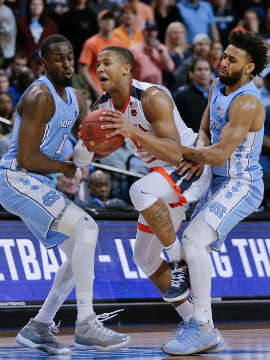 Virginia guard Devon Hall (0) is double-teamed by North Carolina forward Theo Pinson (1) and guard Joel Berry II (2) during the second half of an NCAA college basketball game for the Atlantic Coast Conference men's tournament title Saturday, March 10, 2018, in New York. Virginia won 71-63. (AP Photo/Julie Jacobson)