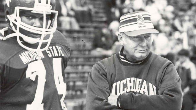 """MSU head football coach Frank """"Muddy"""" Waters, right, stands with one of his players, Kalvin Perkins, on the Spartan Stadium sidelines in 1981. Waters was coach from 1980-1982."""